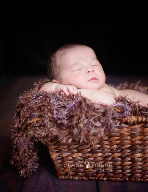 a sleeping, naked, newborn baby asleep in a basket on top of a wooden floor