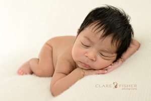 Newborn portrait of baby sleeping on arms