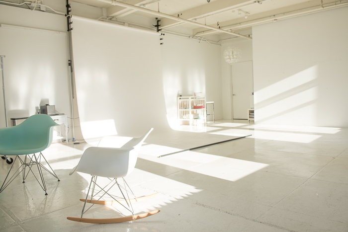 A photograph of a completely white photography studio space with sun streaming in across the floor.