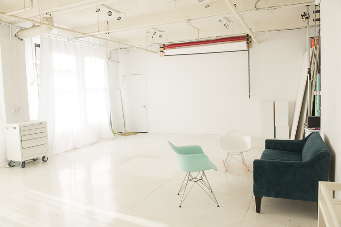 A seating area within a white photography studio.