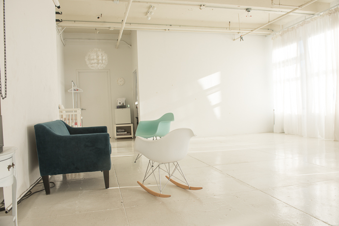 A white, daylight filled photography studio with a seating area.