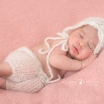 a newborn baby girl with an open weave knit pair of pants and hat in white lying on a pale pink knit blanket.