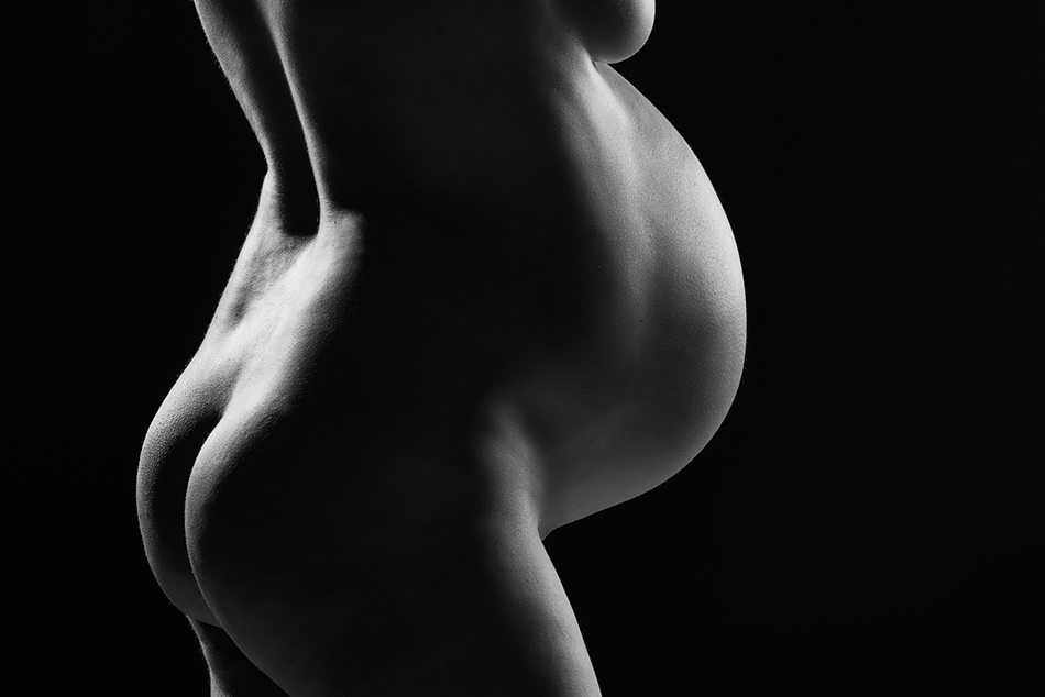 A black and white photograph of a caucasian woman's belly and rear end, lit along the edges of her body against a black background.