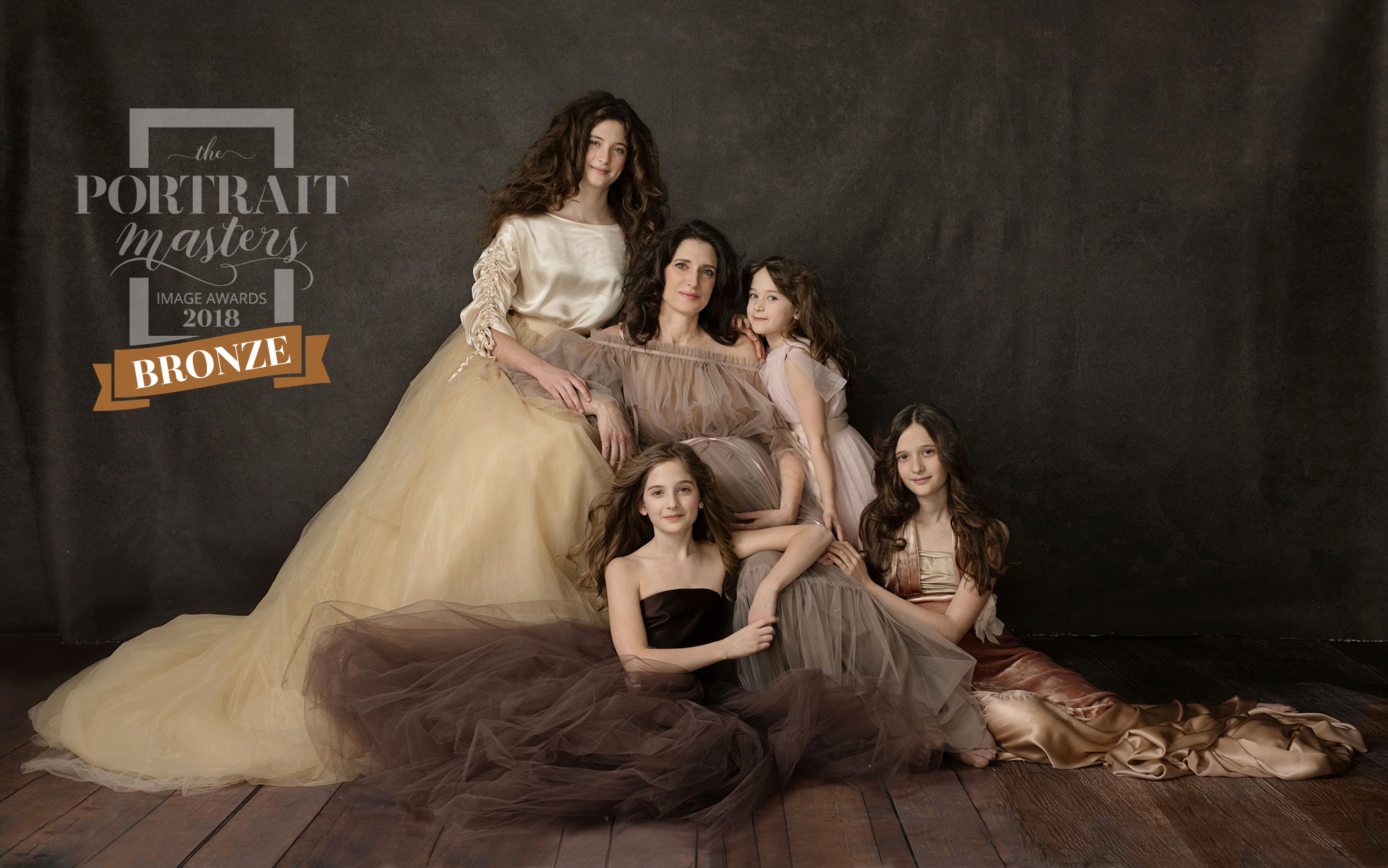 An award winning image of a pregnant mother and her four daughters, all in evening wear in neutral shades of browns and blush seated on boxes and the floor