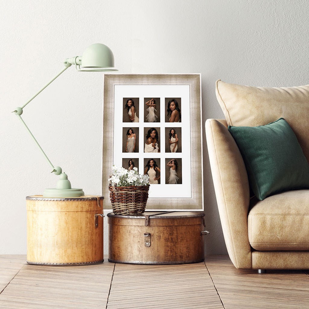 A matted and framed collection of nine images in a golden frame resting on a box beside a couch.