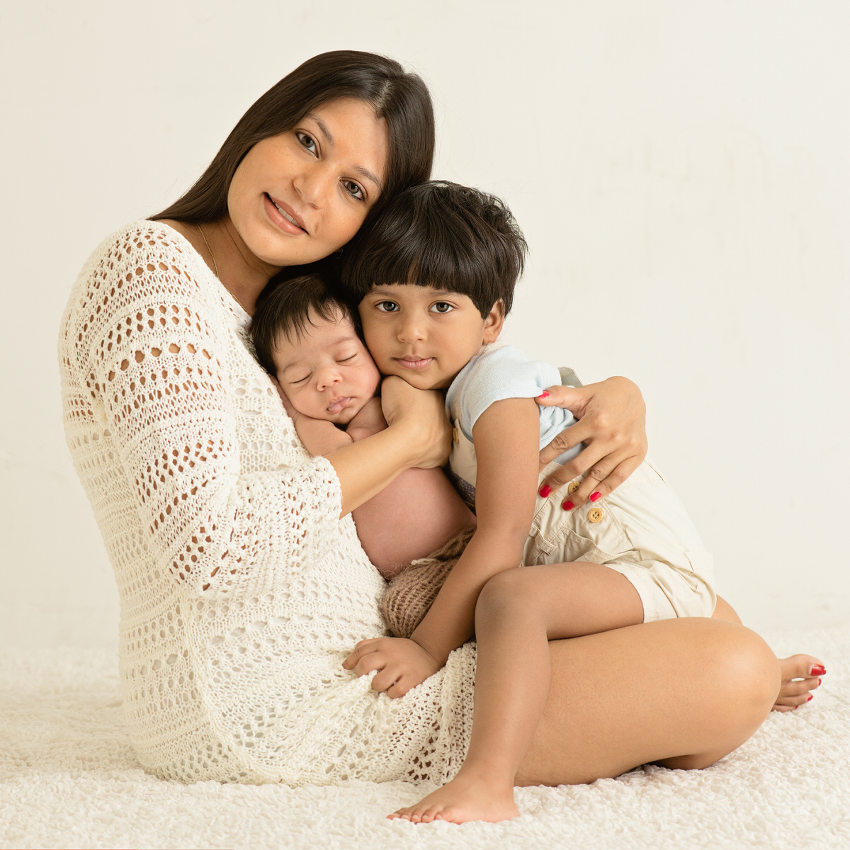 A mother wearing a crochet dress holding her newborn and toddler