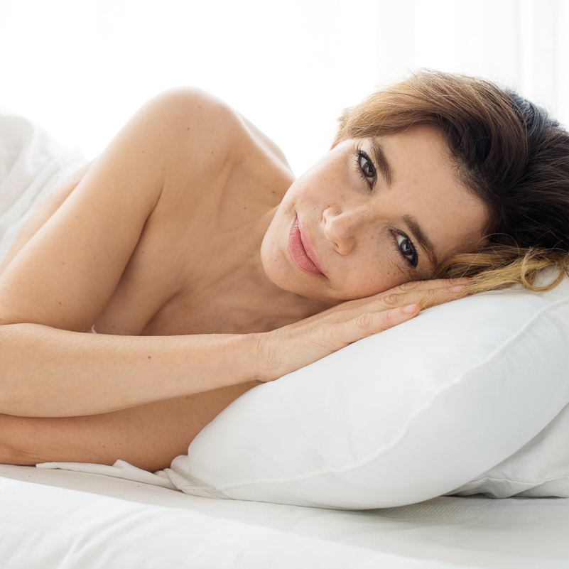 a beautiful brunette, lying down on a white bed and pillow covered in a white sheet