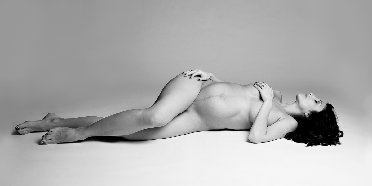 black and white image of a nude woman lying down