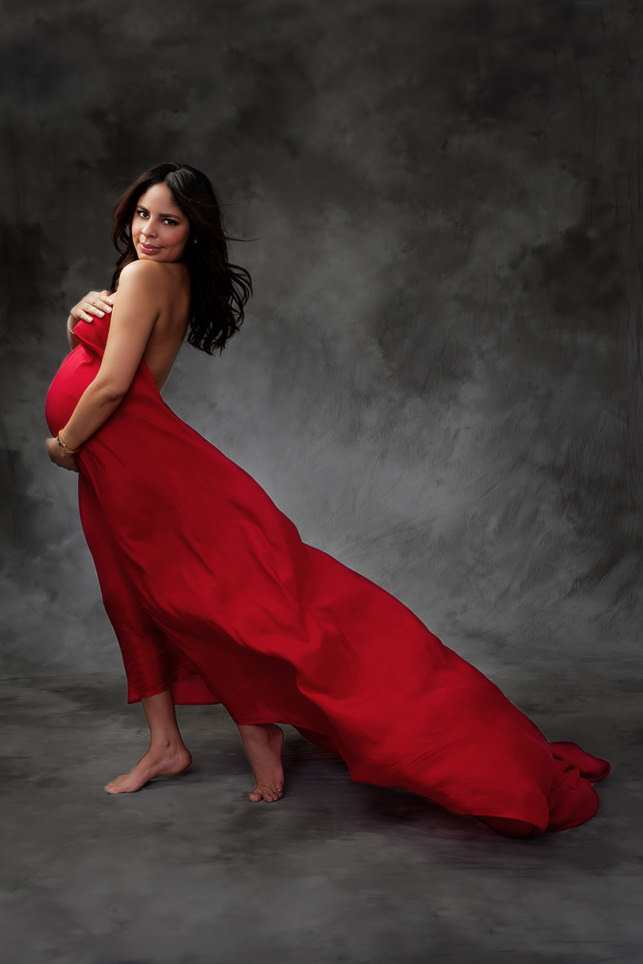 Red fabric flowing out behind a pregnant woman against a gray background