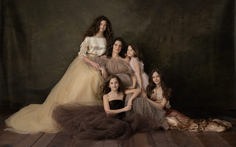 a pregnant woman with her four daughters in gowns
