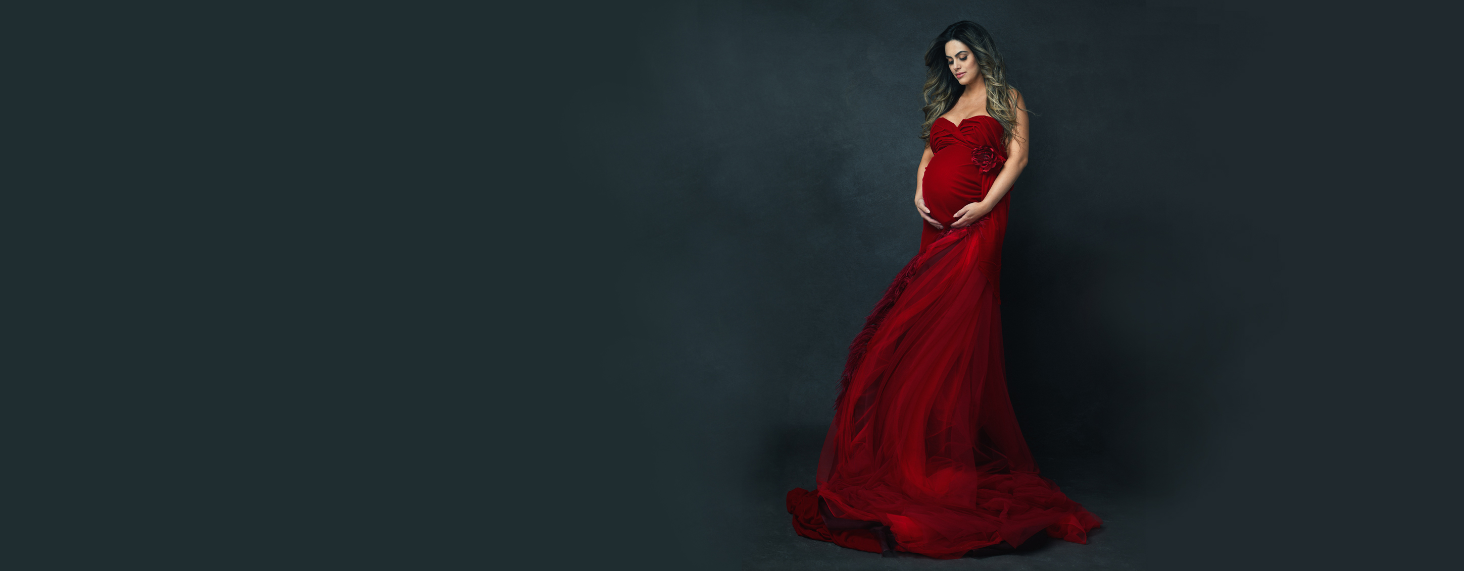 a dramatic portrait of a pregnant woman wearing a red flowing gown