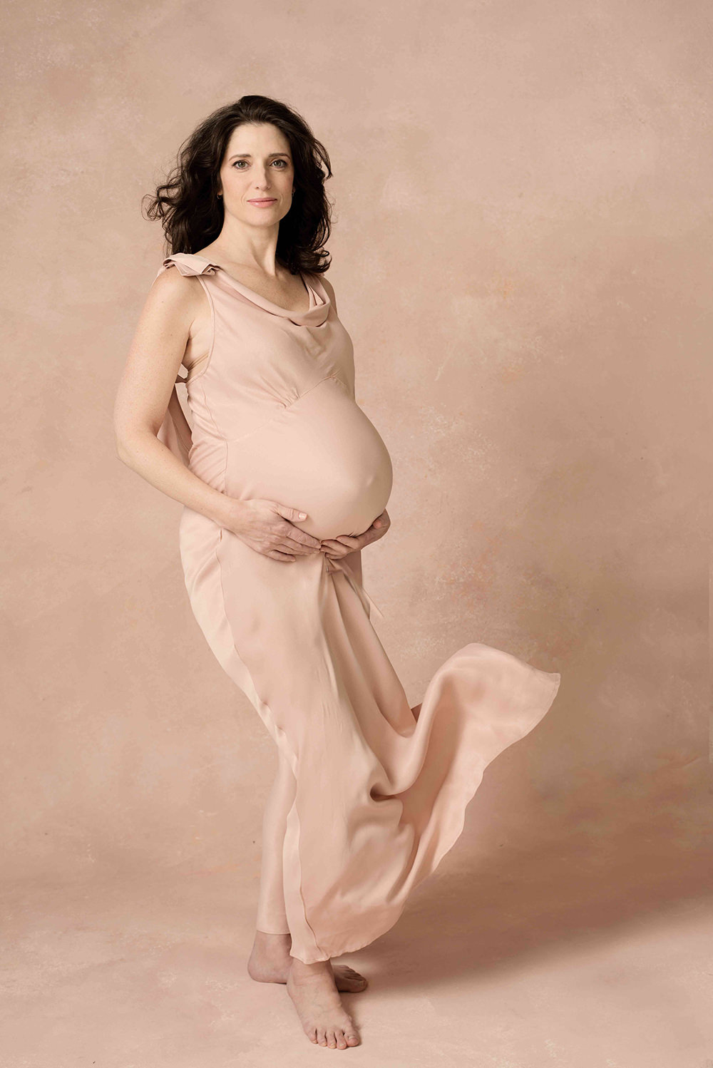 brunette pregnant woman wearing a blush dress against a blush background