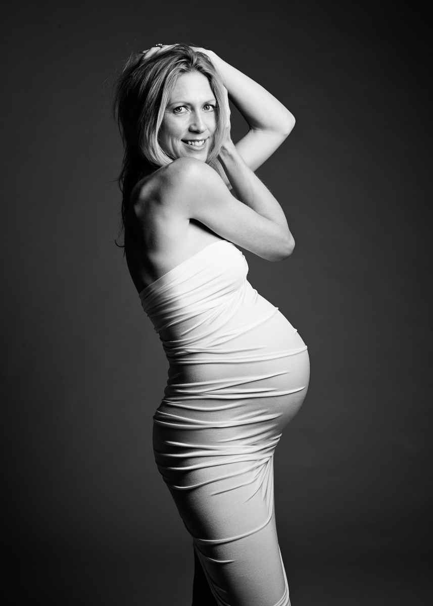 black and white maternity session of woman wearing white dress