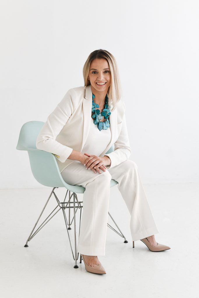 Sava of Avance Organizing sitting on an aqua chair wearing a cream suit with a turquoise necklace