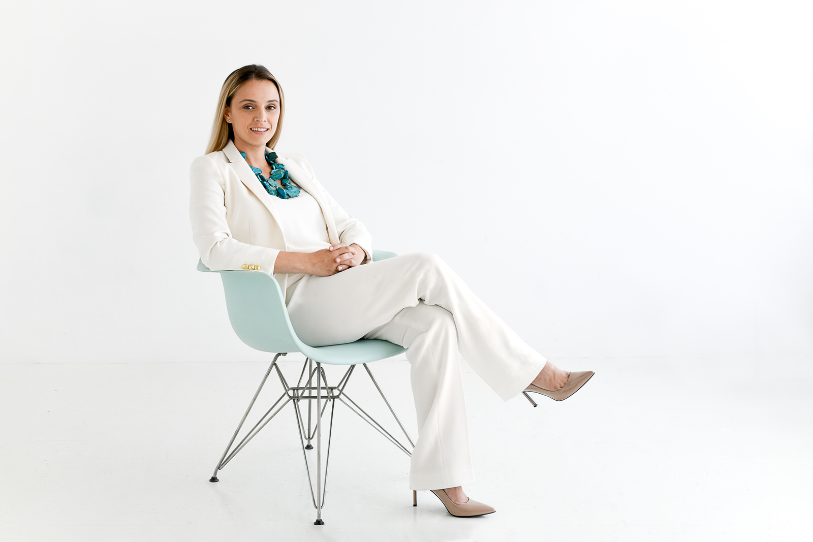 Kon Mari expert Sava wearing a cream suit and turquiose necklace in a white room