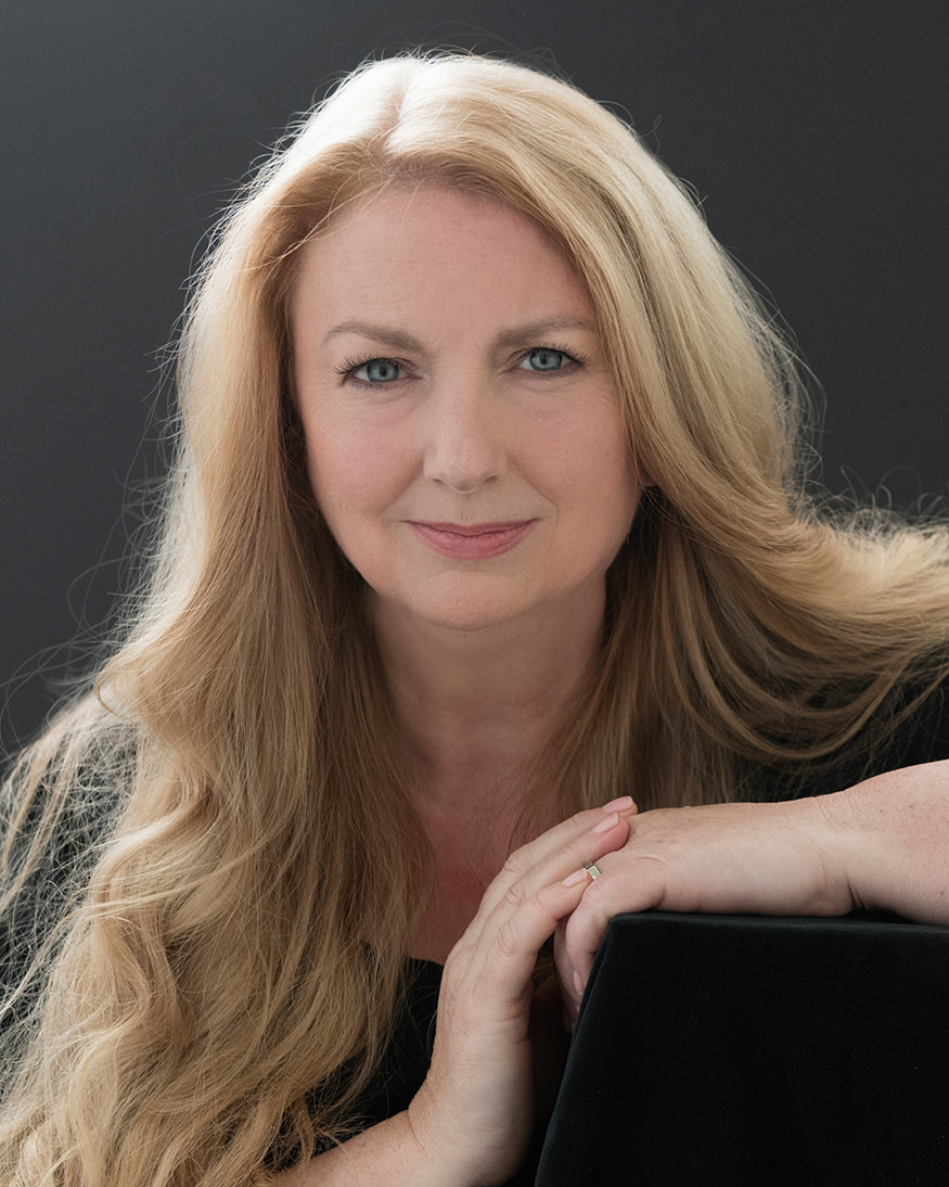 portrait of Clare Fisher wearing a dark dress against a black background