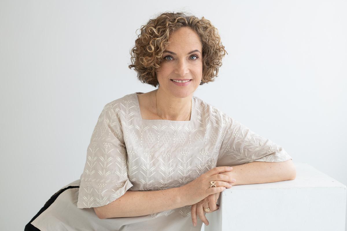 Architect Dorit Zemer leaning on a white box with a white background