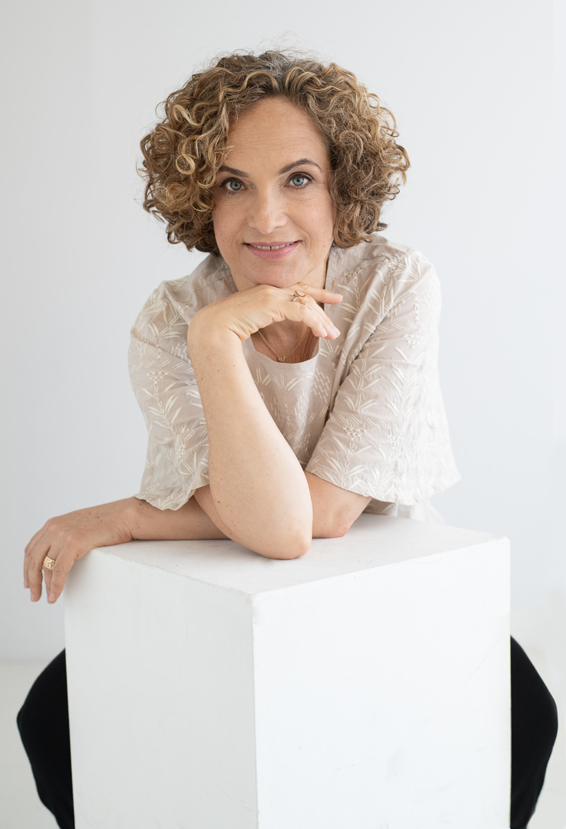 Dorit Zemer leaning on a white box with her hand beneath her chin against a white background
