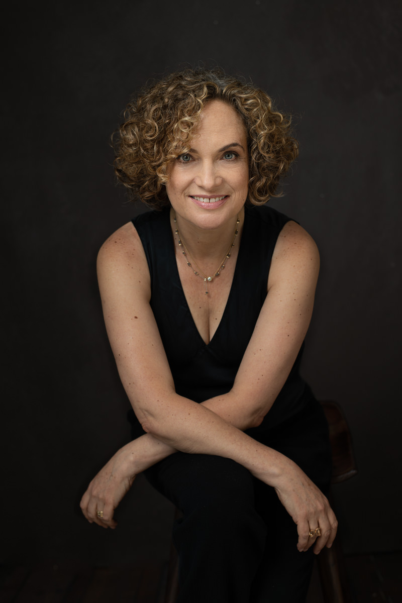 Dorit Zemer in black against a black background leaning on her knees