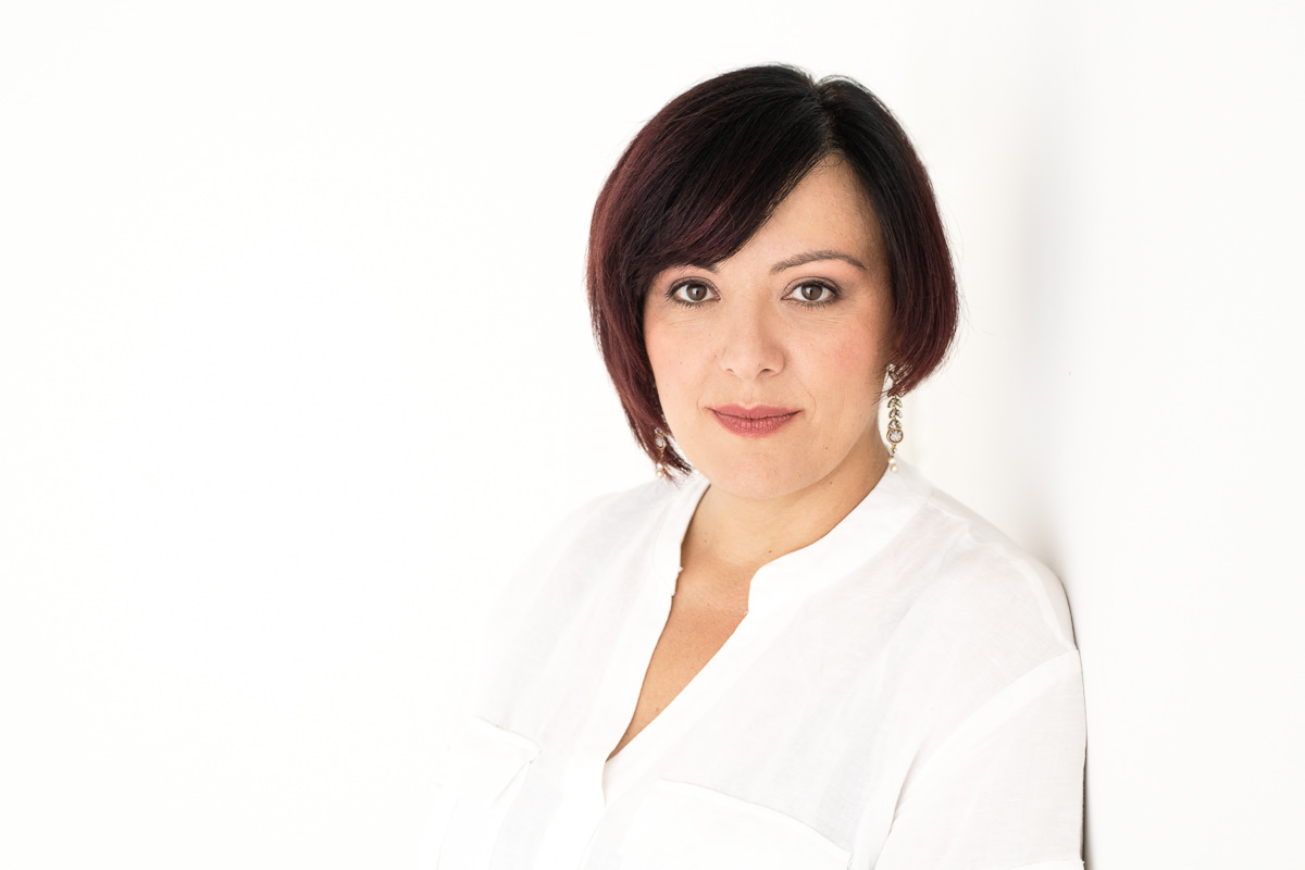 Headshot of Irene Magistro wearing a white top leaning against a white wall