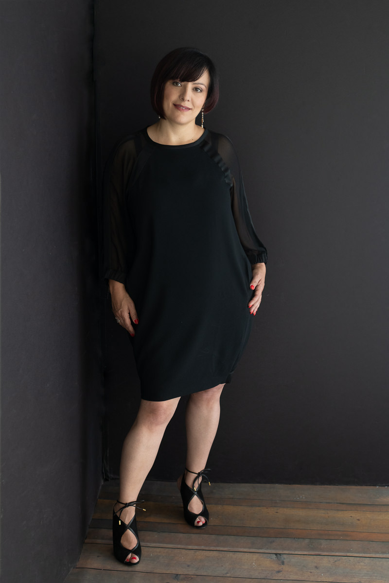 Irene Magistro wearing a black dress standing in a black corner