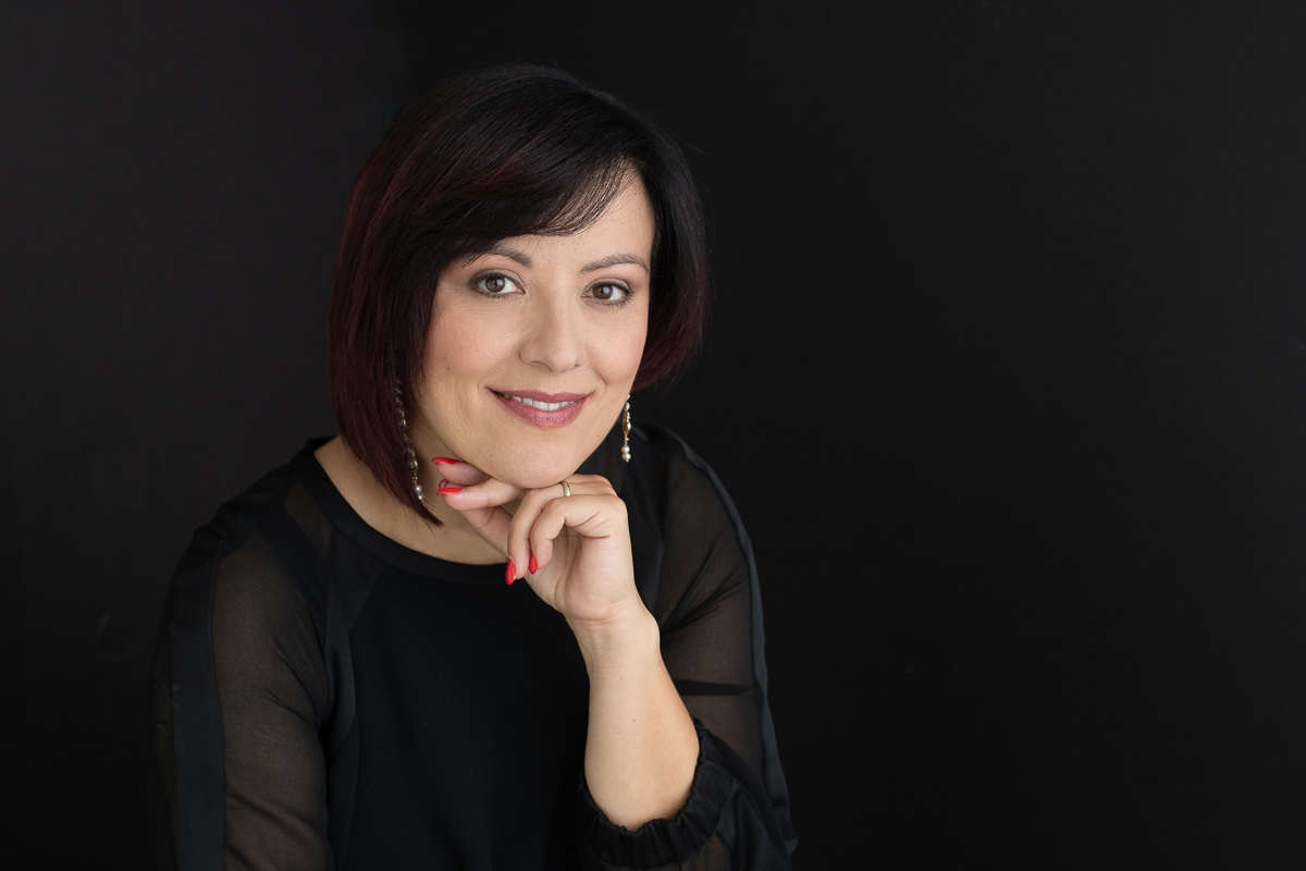 Irene Magistro resting her chin on her hand against a black background