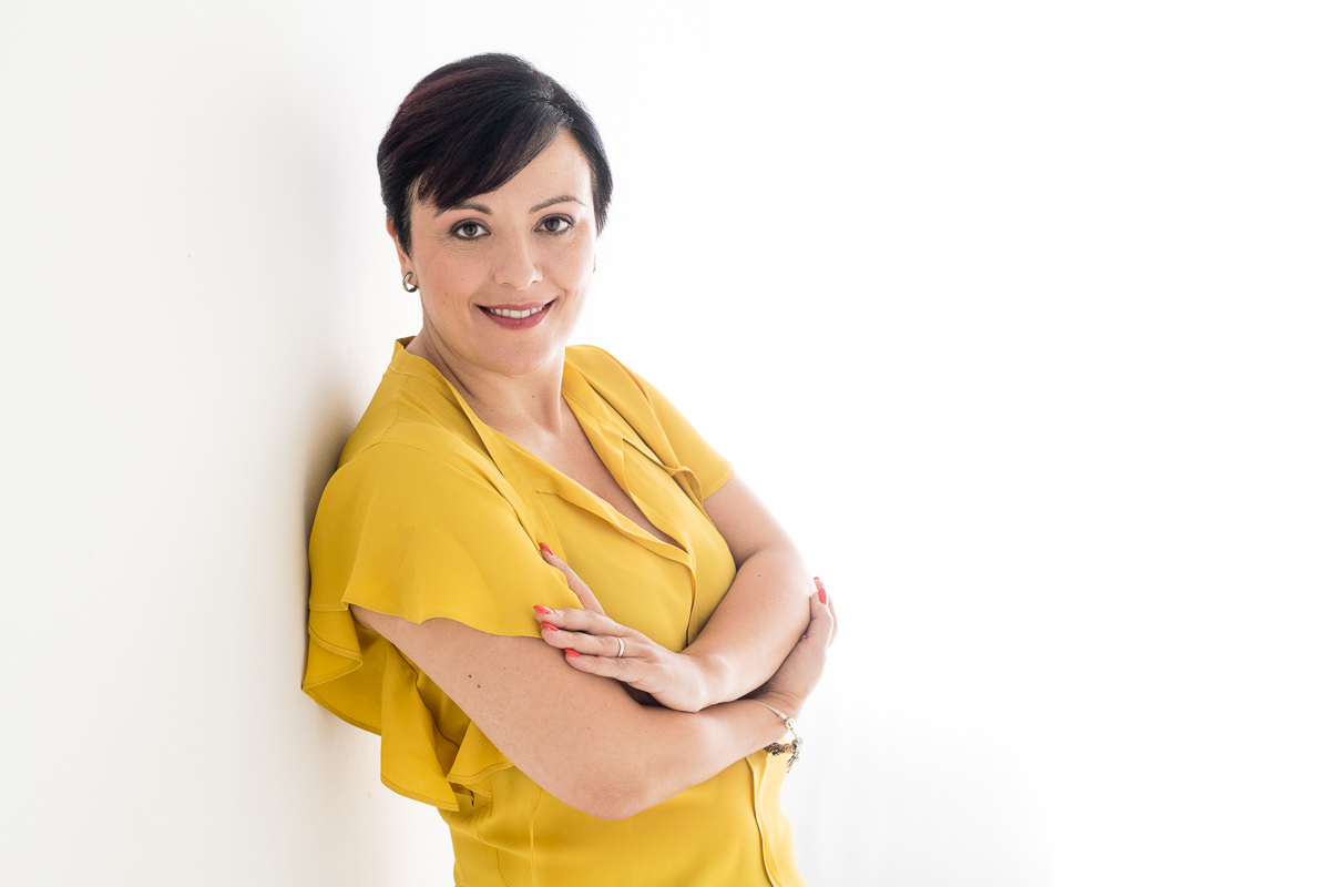 Irene Magistro wearing a yellow blouse and black pants leaning against a white wall