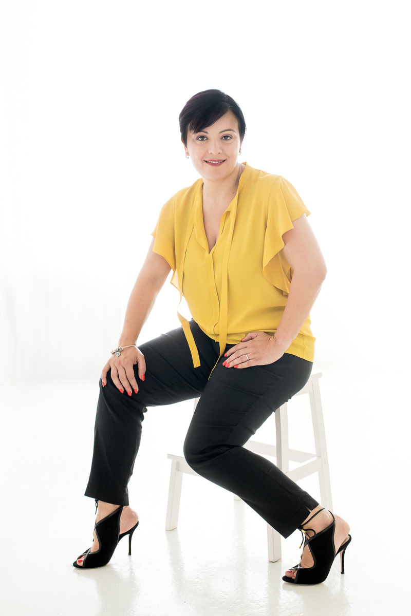 Irene Magistro sitting on a white stool wearing a yellow blouse and black pants in a white room