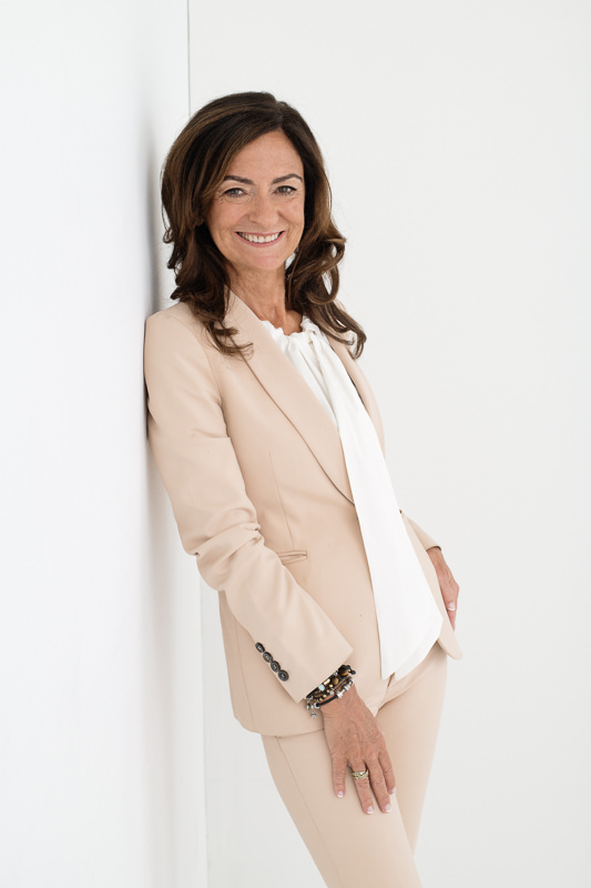 Personal coach Jasmine Bilali wearing a peach suit leaning against a white wall