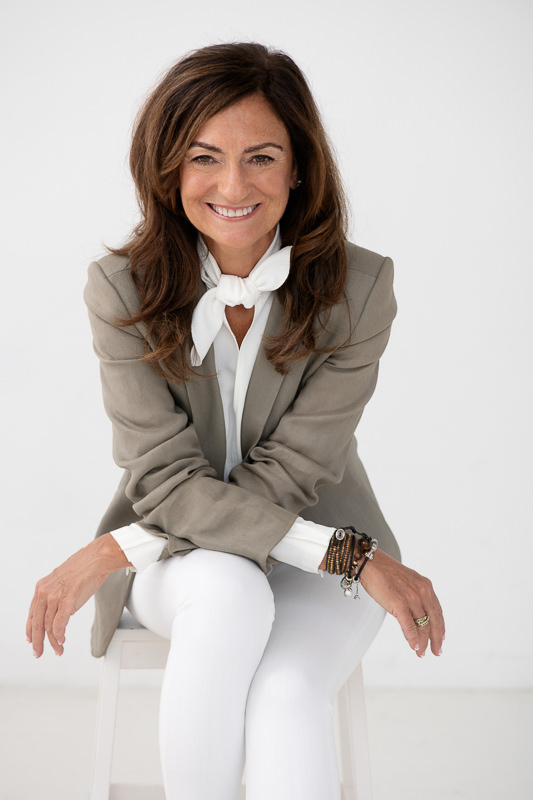 Jasmine Bilali sitting on a stool wearing a taupe jacket and white pants