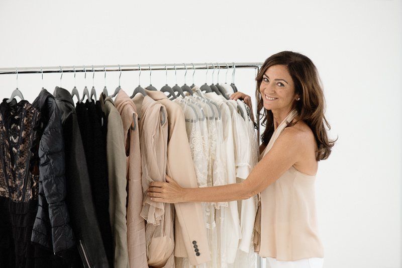 life coach and organizer Jamine Bilali sorting clothes on hanging rack
