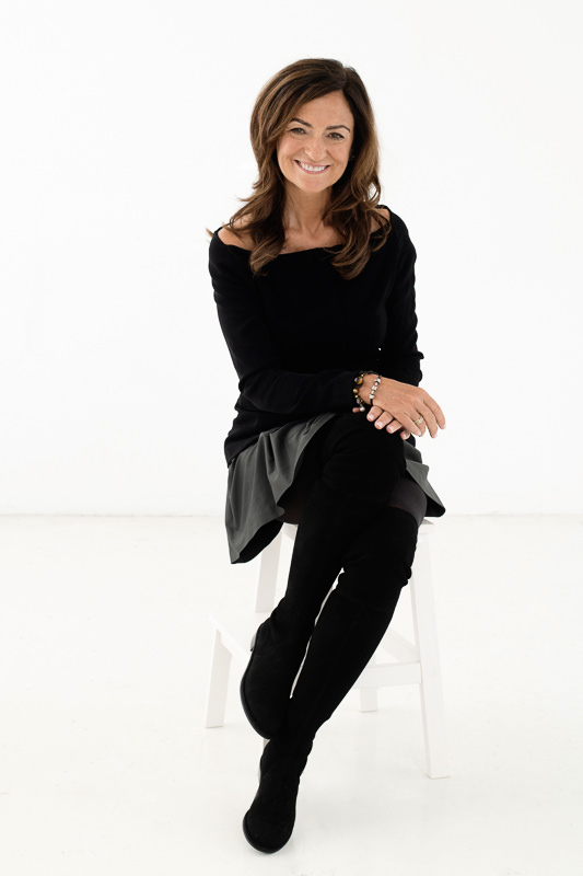 Life coach Jasmine Bilali wearing black and gray sitting on a stool on a white background