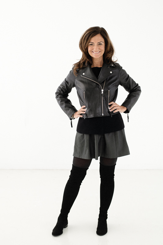 Life coach Jasmine Bilali wearing a black leather jacket and gray skirt against a white background
