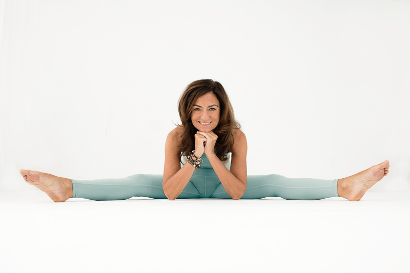 Life coach Jasmine Bilali casually doing the splits in an aqua outift against a white background