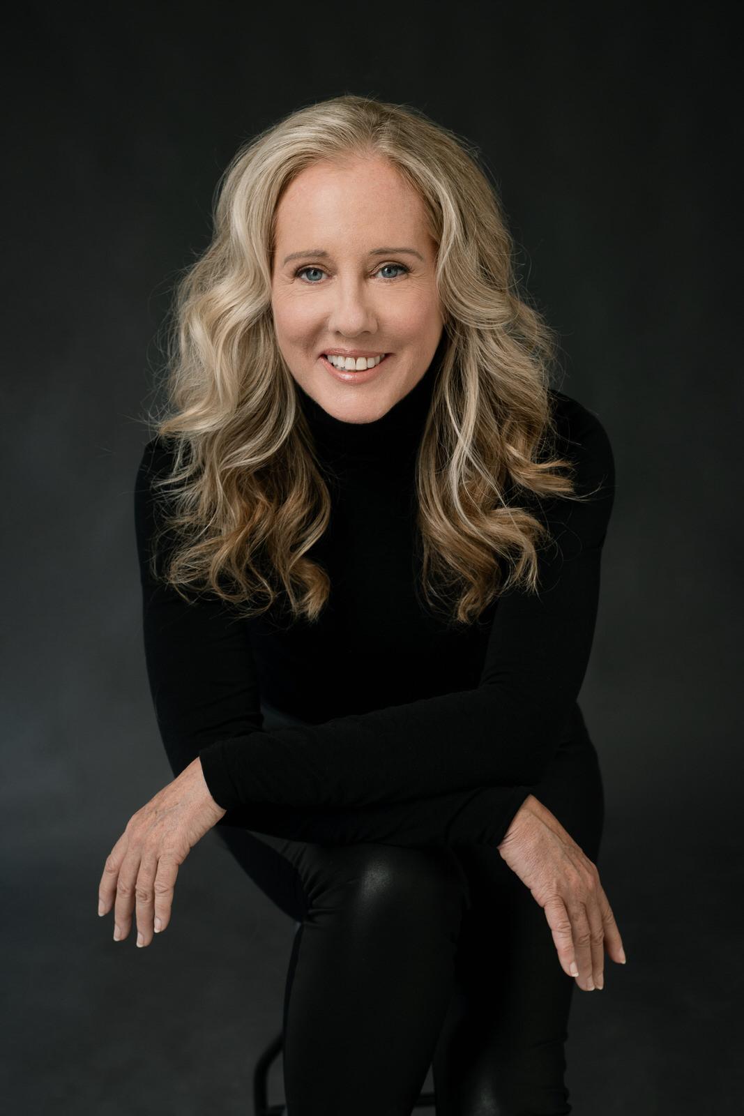 Photographer Jean Nestares wearing a black turtleneck and black pants against a black background