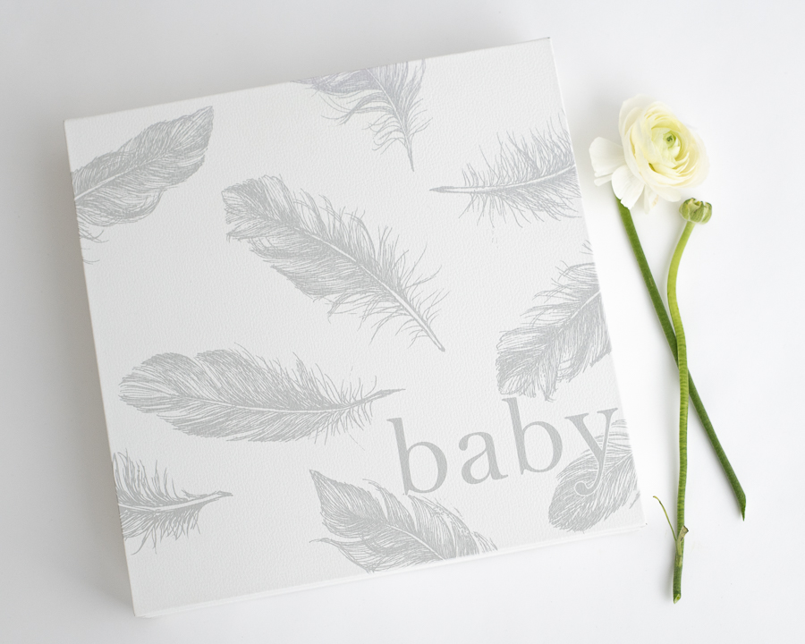 white leather album box with print of gray feathers
