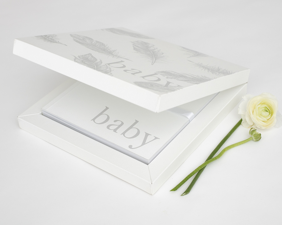 White leather baby album inside white box with feather pattern