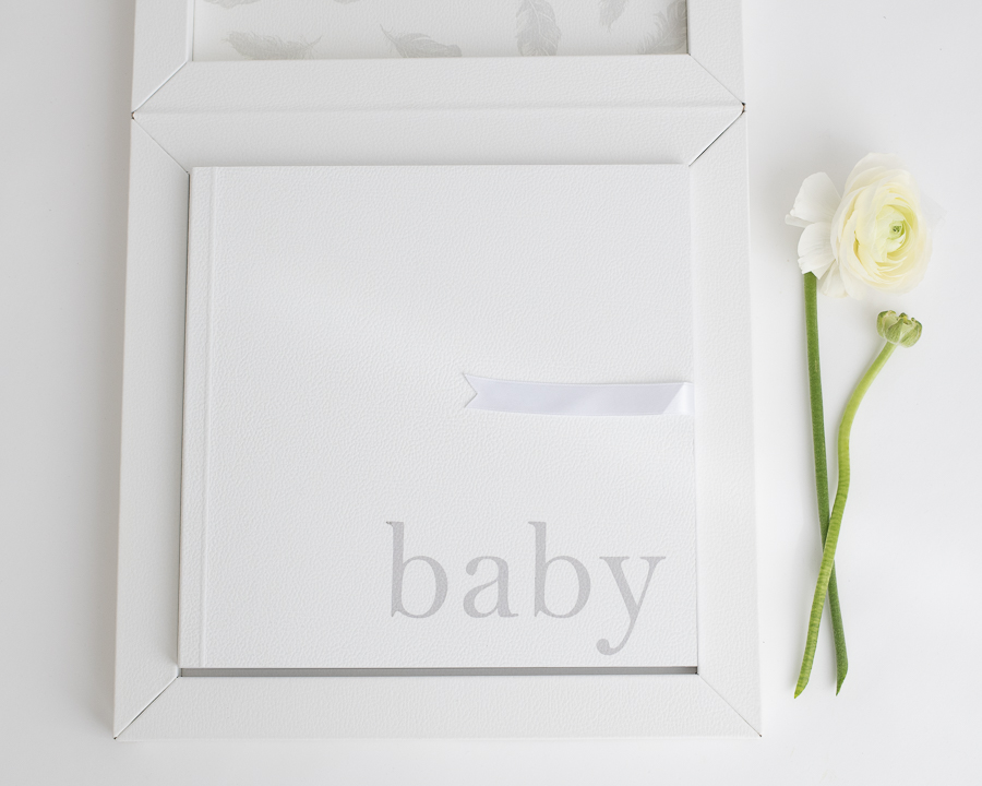 White baby album with gray lettering inside a white custom box