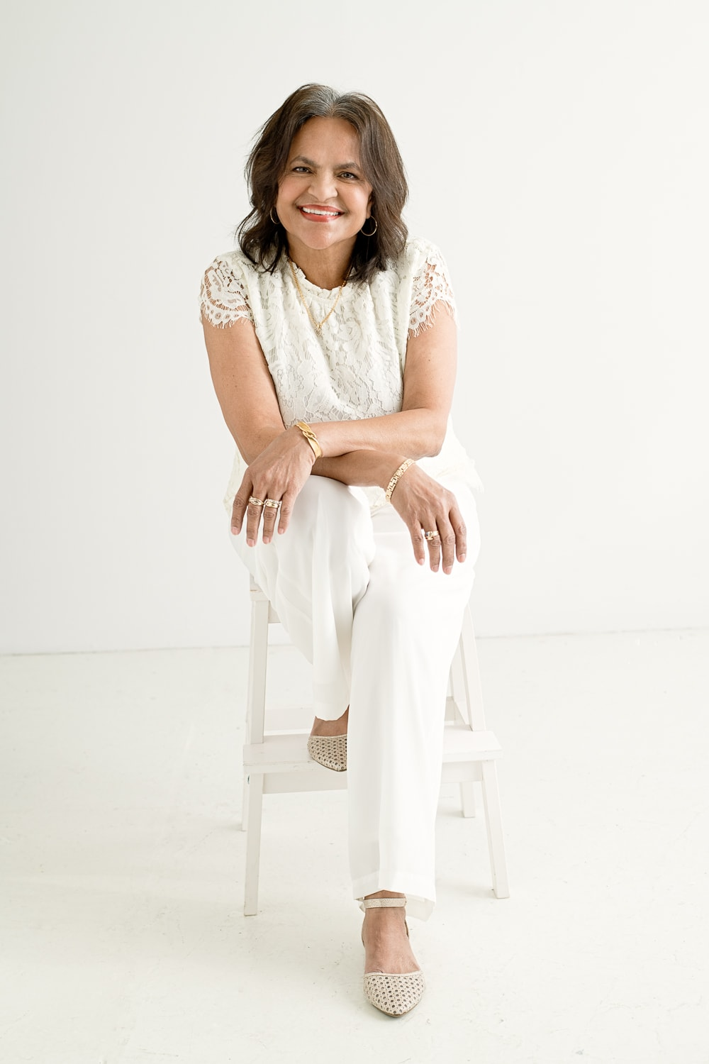 seated woman wearing white against a white background. 50 over 50 project