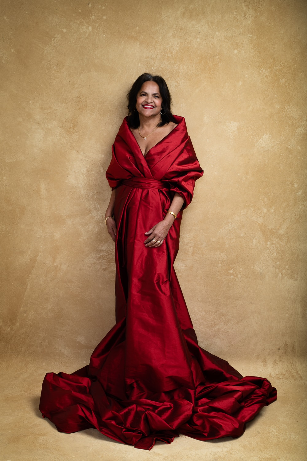 Woman wearing a red gown against a golden brown backdrop